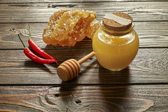 Honey and honeycomb with chili pepper and stick. On wooden background Stock Photo