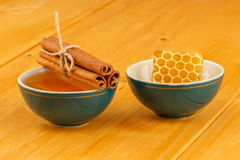 Honey, honeycomb and cinnamon in bowls. Honey, honeycomb and cinnamon sticks in two green porcelain bowls on wooden tabletop surface Stock Image