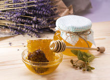 Honey with honeycomb. A jar of honey on wooden surface. Background with lavender flowers. Linden honey. Flower honey. Jar of honey with lid Stock Image