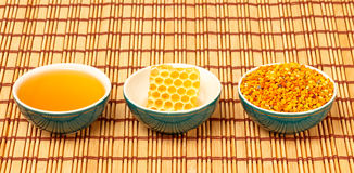 Honey, honeycomb and pollen in bowls. Honey, honeycomb and pollen granules in green porcelain bowls in a row, on light rustic mat Royalty Free Stock Photography