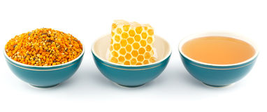 Honey, honeycomb and pollen in bowls. Honey, honeycomb and pollen granules in green porcelain bowls in a row, on white isolated background Stock Photography
