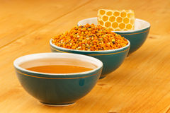 Honey, honeycomb and pollen in bowls. Honey, honeycomb and pollen granules in green porcelain bowls in a row, on wooden tabletop surface stock photo