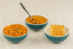 Honey, honeycomb and pollen in bowls. Honey, honeycomb and pollen granules in green porcelain bowls on rustic table cloth stock photo