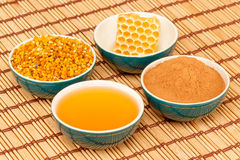 Honey, honeycomb, pollen and cinnamon in bowls. Honey, honeycomb, pollen granules and cinnamon in green porcelain bowls, on light rustic mat Stock Photos