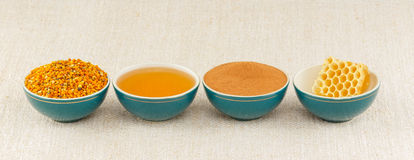 Honey, honeycomb, pollen and cinnamon in bowls. Honey, honeycomb, pollen granules and cinnamon in green porcelain bowls in a row, on rustic table cloth royalty free stock photos