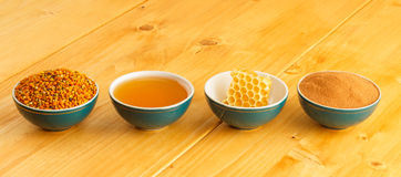 Honey, honeycomb, pollen and cinnamon in bowls. Honey, honeycomb, pollen granules and cinnamon in green porcelain bowls in a row, on wooden tabletop surface Royalty Free Stock Images