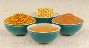 Honey, honeycomb, pollen and cinnamon in bowls. Honey, honeycomb, pollen granules and cinnamon in green porcelain bowls, on rustic table cloth royalty free stock photos