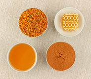 Honey, honeycomb, pollen and cinnamon in bowls. Honey, honeycomb, pollen granules and cinnamon in green porcelain bowls, seen from above, on rustic table cloth royalty free stock photography