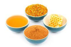 Honey, honeycomb, pollen and cinnamon in bowls. Honey, honeycomb, pollen granules and cinnamon in green porcelain bowls, on white isolated background Stock Images