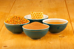 Honey, honeycomb, pollen and cinnamon in bowls. Honey, honeycomb, pollen granules and cinnamon in green porcelain bowls, on wooden tabletop surface stock photos