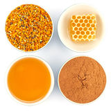 Honey, honeycomb, pollen and cinnamon in bowls. Honey, honeycomb, pollen granules and cinnamon in porcelain bowls, seen from above, on white isolated background stock photos