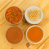 Honey, honeycomb, pollen and cinnamon in bowls. Honey, honeycomb, pollen granules and cinnamon in porcelain bowls, seen from above, on wooden tabletop surface stock photos