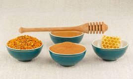 Honey, honeycomb, pollen granules and cinnamon in bowls. Pollen granules, honeycomb, honey and cinnamon in green porcelain bowls with wooden dipper, on rustic Royalty Free Stock Images