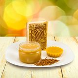 Honey, honeycomb and pollen on the table Stock Photos