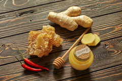 Honey and honeycomb with spices and stick. On wooden background Royalty Free Stock Image