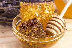 Honey with honeycomb on wooden surface. Background with lavender flowers Royalty Free Stock Photos