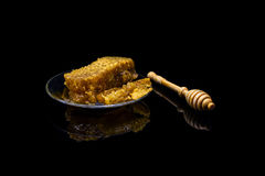 Honey with honeycombs on a glass plate isolated on a black background. Honey with honeycombs on a glass plate on a black background stock photos