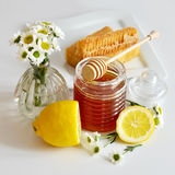 Honey. With combs lemons and flowers, selective focus Stock Image