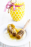 Honey with honeycombs. Honey from the honeycombs on a plate and a jar of honey Royalty Free Stock Image