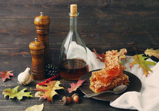 Honey in honeycombs on a plate, wine in a bottle and pepper mill of wood on a wooden surface Stock Photo