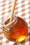 Honey immerse with wood dipper Royalty Free Stock Photos