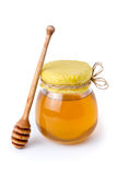 Honey jar. A jar of sweet flower honey with honeycomb lid and wooden drizzler Royalty Free Stock Photo