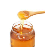 Honey Jar. With wooden spoon, isolated on white Royalty Free Stock Image