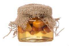 A honey jar with almonds nuts. On a white background isolation Stock Image