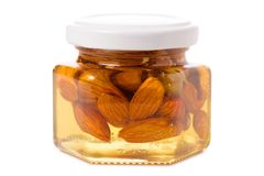 A honey jar with almonds nuts. On a white background isolation Stock Photos
