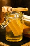 Honey with honey comb in a jar. Honey in a jar with honey comb inside Royalty Free Stock Images