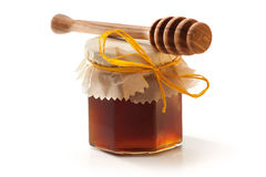 Honey Jar and dipper. Honey Jar with wooden dipper on white background stock photo