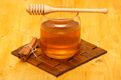 Honey in jar with dipper and cinnamon bars. Honey in glass jar with wooden dipper and cinnamon bars on wooden tabletop and mat royalty free stock photo