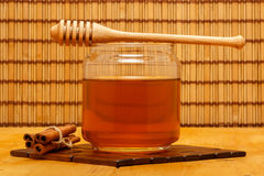 Honey in jar with dipper and cinnamon bars. Honey in glass jar with wooden dipper and cinnamon bars on wooden tabletop and mat, with straw mat backdrop stock image