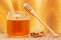 Honey in jar with dipper, cinnamon and honeycomb o. Honey in glass jar with wooden dipper and cinnamon sticks on light rustic mat with honeycomb background Royalty Free Stock Photography