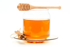 Honey in jar with dipper and cinnamon on isolated background. Honey in glass jar with wooden dipper and cinnamon sticks on white isolated background royalty free stock images