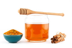 Honey in jar with dipper, cinnamon , pollen on isolated background. Honey in glass jar with wooden dipper, cinnamon sticks, pollen granules in porcelain bowl on royalty free stock image