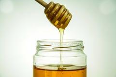 Honey jar with dipper. Honey descending from an honey dipper in a jar Stock Photo