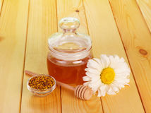Honey jar with dipper and flower Stock Image