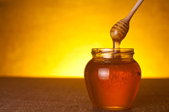 Honey jar with dipper. And flowing honey stock photo