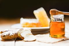 Honey in jar with honey dipper ginger on wooden and honeycomb on white plate background stock image