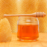Honey in jar with dipper on honeycomb background. Honey in glass jar with wooden dipper on honeycomb background and wood surface royalty free stock images