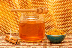Honey in jar with dipper, honeycomb, cinnamon and. Honey in glass jar with wooden dipper, cinnamon sticks and pollen granules in green porcelain bowl on light Stock Photography