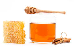 Honey in jar with dipper, honeycomb, cinnamon on isolated background Stock Photos