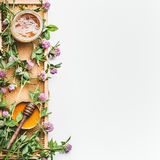 Honey in jar with dipper, honeycomb frame and wild flowers on white background, top view royalty free stock images