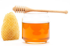 Honey in jar with dipper and honeycomb on isolated background. Honey in glass jar with wooden dipper and honeycomb on white isolated background royalty free stock photo