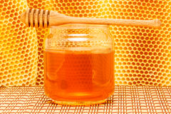 Honey in jar with dipper and honeycomb on mat. Honey in glass jar with wooden dipper on light rustic mat with honeycomb background Royalty Free Stock Photography