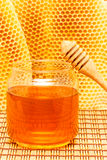 Honey in jar with dipper and honeycomb on mat. Honey in glass jar with wooden dipper on light rustic mat with honeycomb background royalty free stock image