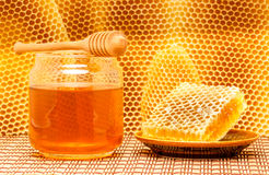 Honey in jar with dipper and honeycomb on mat. Honey in glass jar with wooden dipper and honeycomb on light rustic mat with honeycomb background Stock Photo