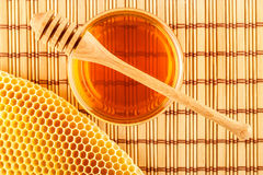 Honey in jar with dipper and honeycomb on mat. Honey in glass jar with wooden dipper and honeycomb on light rustic mat background viewed from above Royalty Free Stock Image