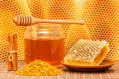 Honey in jar with dipper, honeycomb, pollen and ci. Honey in glass jar with wooden dipper, honeycomb, pollen granules and cinnamon sticks on light rustic mat Royalty Free Stock Photo